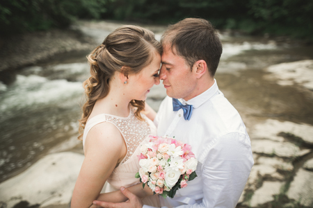 Bride and groom holding beautiful wedding bouquet. Lake and forest. Stock Photo
