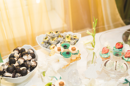 Delicious and tasty dessert table with cupcakes and shots at reception closeup.