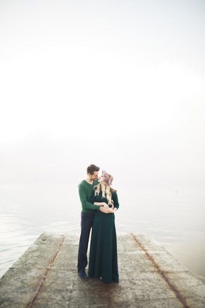 sea dock: Lovely couple kissing and hugging on a sea dock. Stock Photo