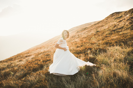 Beautiful bride with a bouquet on mountain background at sunset Stock Photo