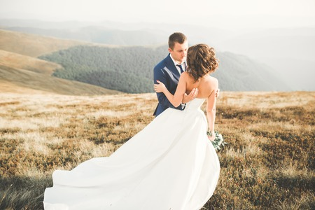 Beautifull wedding couple kissing and embracing near mountain with perfect view Stock Photo