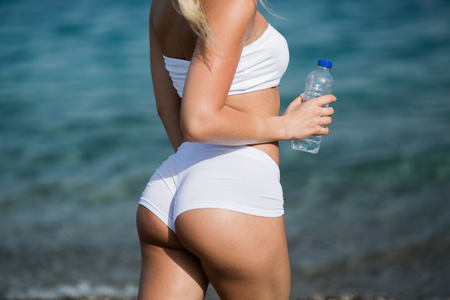 Beautiful young woman with long blond hair in white shorts is standing a back on the coastline of the sea Imagens