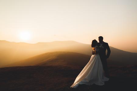 Gelukkig mooi bruiloft paar bruid en bruidegom op trouwdag buitenshuis op de bergen rock. Gelukkig huwelijkspaar buitenshuis op de natuur, zachte zonnige lichten