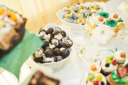 ombre: Delicious and tasty dessert table with cupcakes and shots at reception closeup.