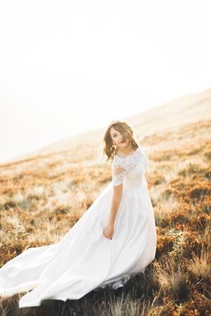 Gelukkige mooie bruid buiten op een zomerweide bij de zonsondergang met perfect uitzicht