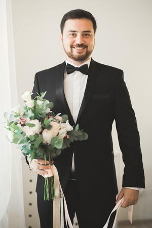dinner jacket: Beautiful man, groom posing and preparing for wedding