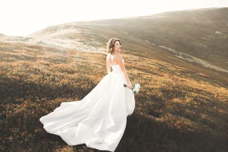 夕日で山を背景に花束と美しい花嫁