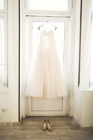 Fashion wedding dress for bride hanging near window. 版權商用圖片