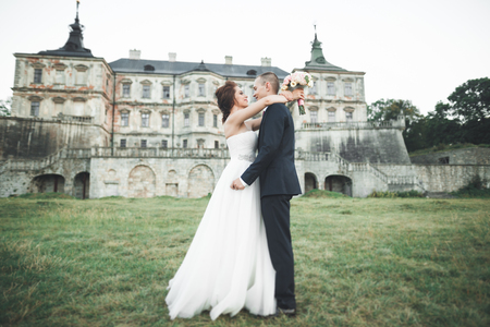 Just married poses and kissing with an old fortress on the background