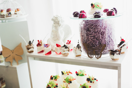 Delicious sweets on wedding candy buffet with desserts, cupcakes. Stock Photo