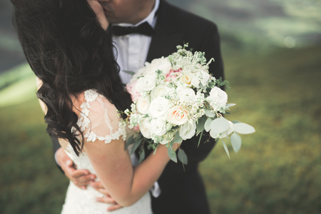 Pretty good wedding bouquet of various flowers in hand.