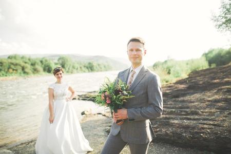 Sposa e sposo che tiene bella sposa bouquet in posa vicino al fiume Archivio Fotografico - 84287241