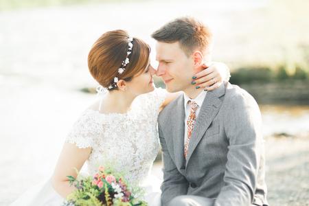 Sposa e sposo che tiene bella sposa bouquet in posa vicino al fiume Archivio Fotografico - 84287367