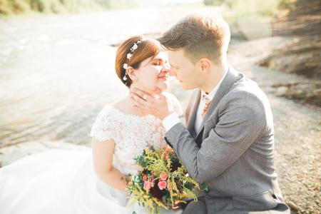 Sposa e sposo che tiene bella sposa bouquet in posa vicino al fiume Archivio Fotografico - 84287362