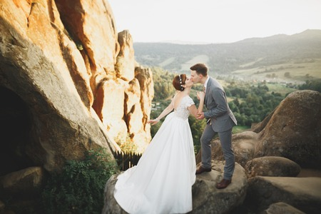 Beautiful wedding couple, bride and groom, in love on the background of mountains