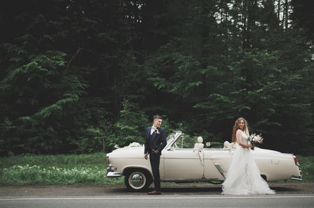 Stijlvol bruiloftspaar, bruid, bruidegom kussen en knuffelen op retro auto Stockfoto