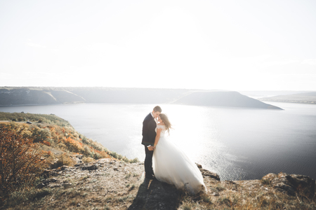 Elegant stylish happy wedding couple, bride, gorgeous groom on the background of sea and sky Stock Photo