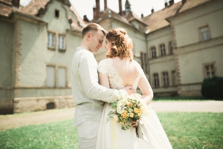 Beautiful romantic wedding couple of newlyweds hugging near old castle