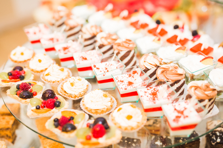 Delicious sweets on wedding candy buffet with desserts, cupcakes. Stock Photo - 85615540