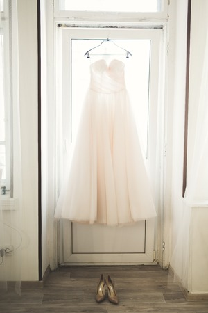 Fashion wedding dress for bride hanging near window. Stock Photo