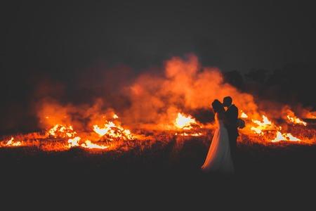 Amazing wedding couple near the fire at night