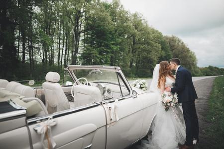 세련 된 웨딩 커플, 신부, 신랑 키스 및 레트로 자동차에 포옹