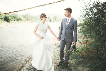 Bride and groom holding beautiful wedding bouquet. Posing near river Imagens - 87381016