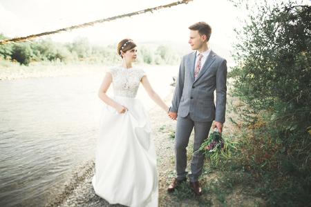 Sposa e sposo che tengono il bello mazzo di nozze. In posa vicino al fiume Archivio Fotografico - 87381016