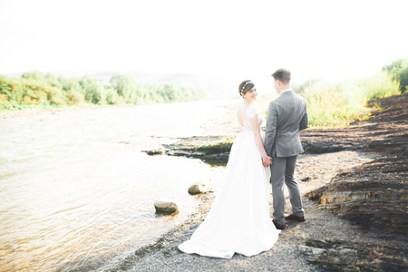 Bride and groom holding beautiful wedding bouquet. Posing near river Stock Photo