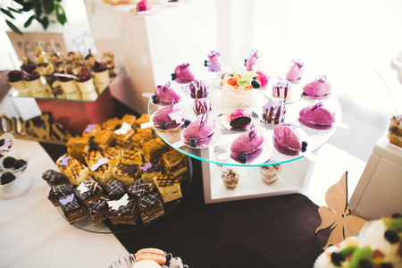 Delicious and tasty dessert table with cupcakes shots at reception closeup Imagens - 87936084