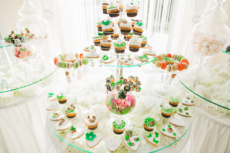 Delicious sweets on wedding candy buffet with desserts, cupcakes Stock Photo - 87936087