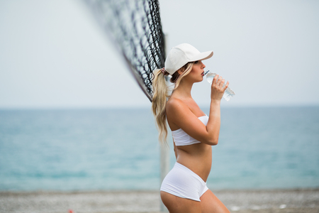 Refreshing after workout. Beautiful young blonde woman in sports clothing drinking water