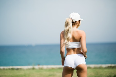 Sexy and fit blonde girl is standing on the shore and watching at sea Imagens