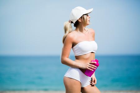해변에 물병과 화려한 맞는 젊은 여자