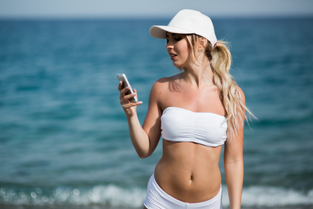 Happy pretty fitness blonde girl is showing cellphone and smiling Stock Photo