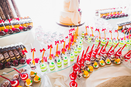 Delicious sweets on wedding candy buffet with desserts, cupcakes Stock Photo - 88172459