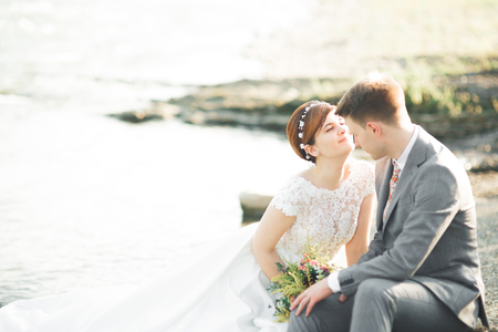 Sposa e sposo che tengono il bello mazzo di nozze. In posa vicino al fiume Archivio Fotografico - 88225786