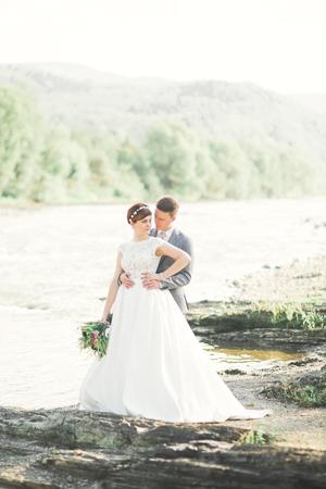 Sposa e sposo che tengono il bello mazzo di nozze. In posa vicino al fiume Archivio Fotografico - 88225797