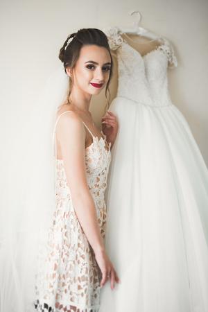 hermosa novia con vestido de novia de moda con plumas con maquillaje
