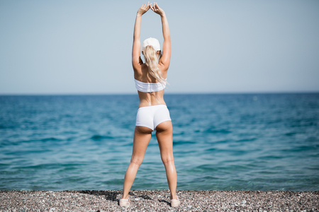 back view of sporty woman doing stretching exercises on the beach