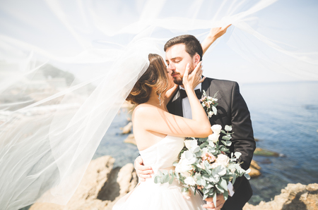 Wedding couple, groom, bride with bouquet posing near sea and blue sky Stockfoto