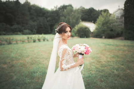 Portrait of stunning bride with long hair posing with great bouquet