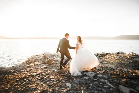 Wedding couple kissing and hugging on rocks near blue sea