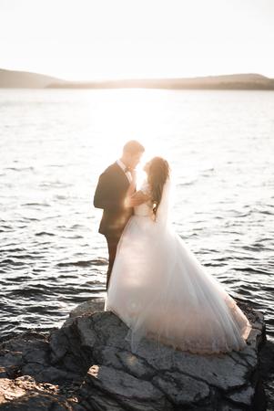 Elegant stylish happy wedding couple, bride, gorgeous groom on the background of sea and sky Stock Photo