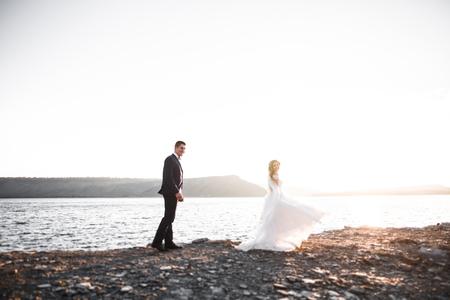 Happy wedding couple staying over beautiful landscape