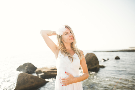 Romantic beautiful bride in white dress posing on the sea stones