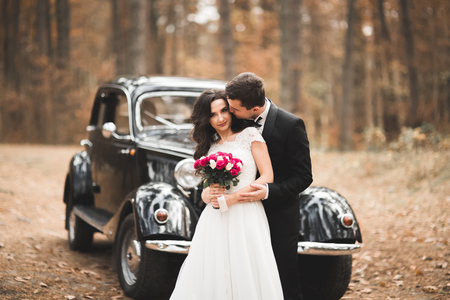 Stylish wedding couple, bride, groom kissing and hugging near retro car in autumn Banque d'images