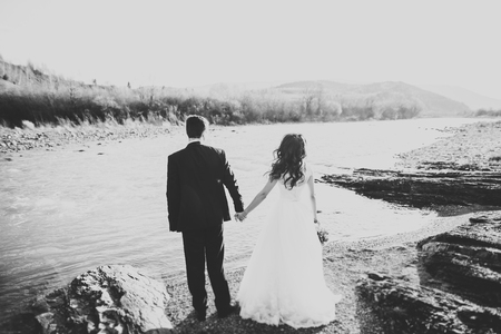 Happy newlywed couple posing and smiling in wedding dress and suit outdoor, black and white Stock Photo