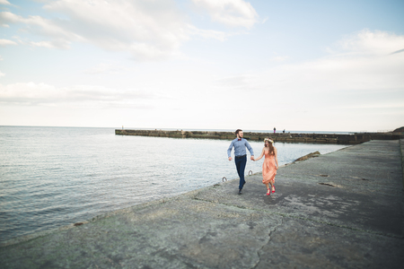 Beautiful loving couple, pride with long dress walking on pier