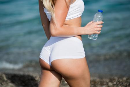 白のショート パンツで長いブロンドの髪を持つ美しい若い女性が海の海岸線に背を立っています。